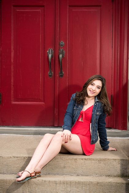 High school senior in a red dress in front of a red door.