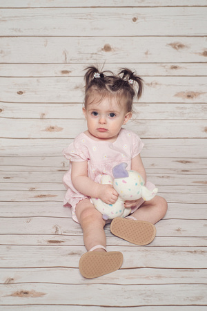 one year old girl on a white wooden backdrop