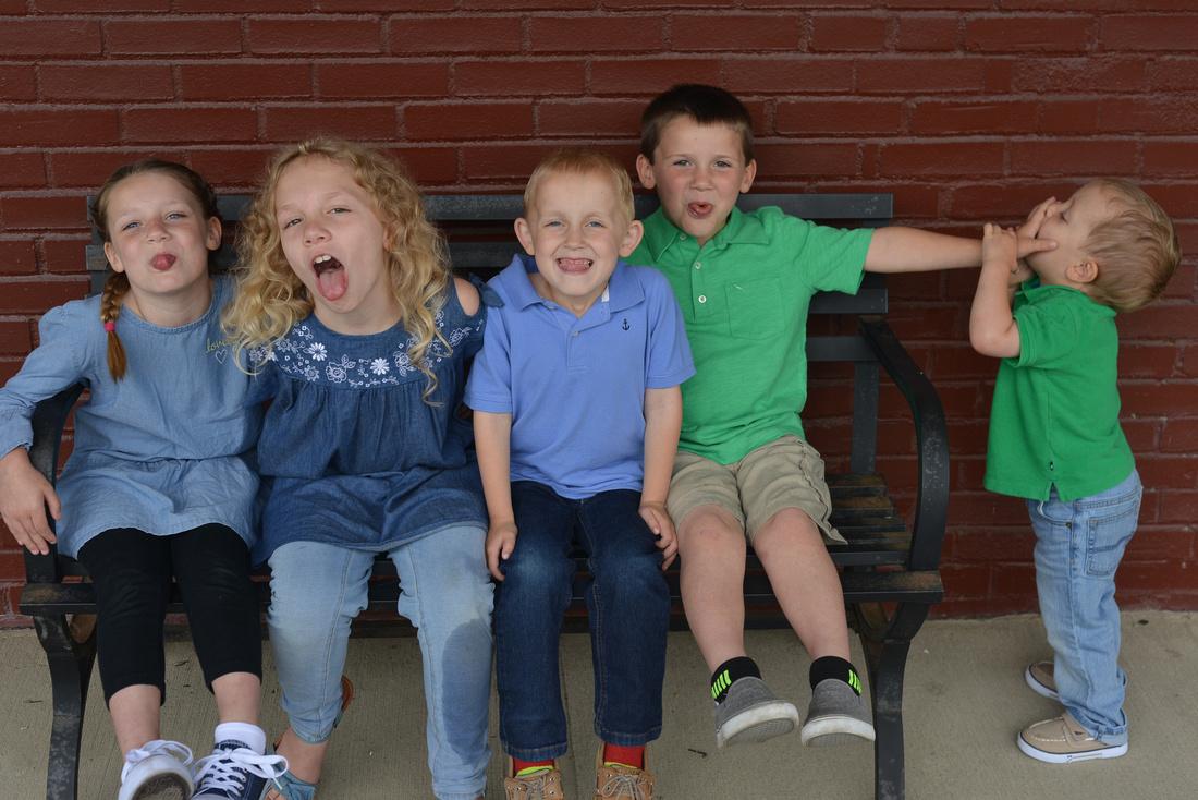 Five children sitting on a bench.