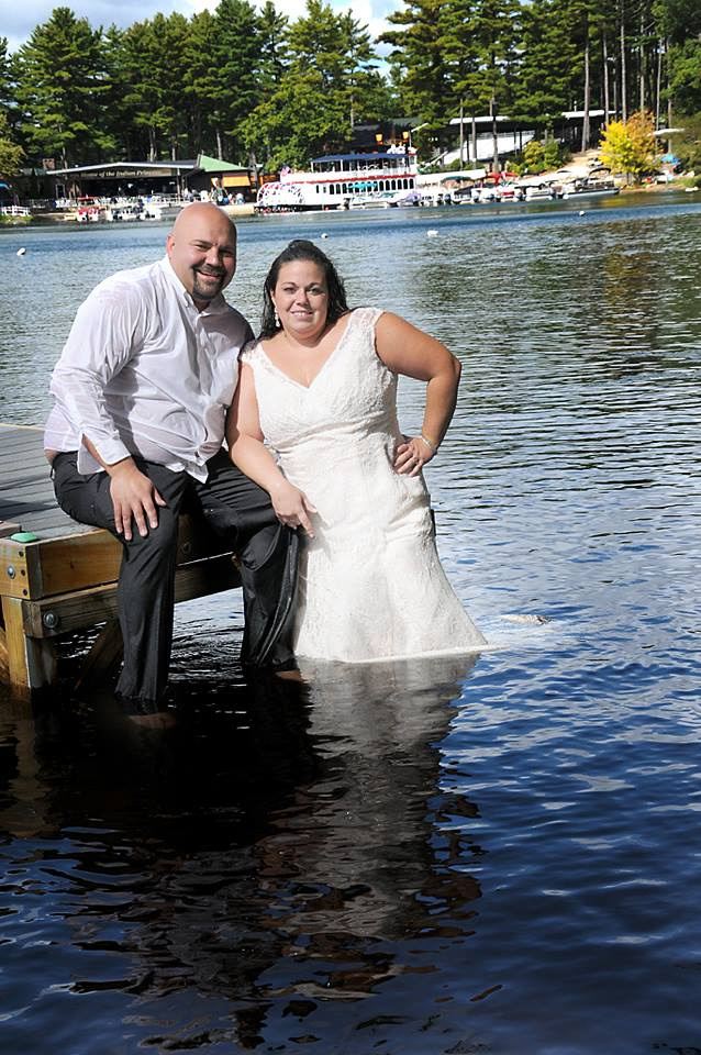 Bride and groom jumping into a lake