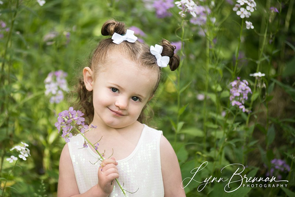 Little girl surrounded by purple flowers.