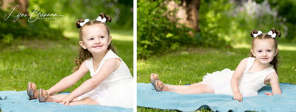 Little girl sitting on a blue blanket.
